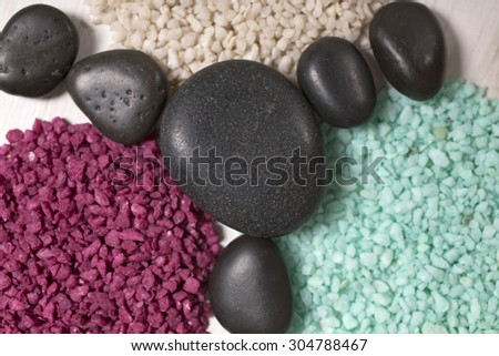 Three piles of white red and blue sand with smooth peoples boring the piles