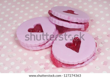three pink jam cookies on a dotted background