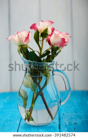 Three pink roses floral arrangement with stems and leaves in a clear glass vase with a white gray and blue background. Bouquet of pink rose flowers in a glass vase on a empty background - stock photo