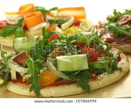 Three pizzas with vegetables ready for baking - stock photo