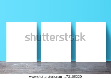 three  placard standing next to a blue wall - stock photo