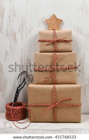 Three plain brown paper wrapped gifts stacked in the shape of a Christmas tree with star. Scissors and ball of twine are next to the packages.