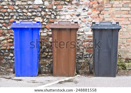 Three plastic bins against a stone wall - stock photo