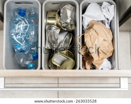 Three plastic trash bins in kitchen cabinet with segregated household garbage - PET bottles, paper and metal cans shot from above - stock photo
