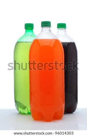 Three plastic two liter soda bottles with condensation on a wet counter. Vertical format over a white background. - stock photo