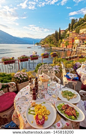 Three plates of lovely vegetarian Italian food on white plates on a table on a lovely outdoor terrace overlooking a beautiful, calm lake, with antique buildings and alpine mountains in the background - stock photo