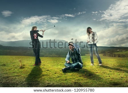Three players play on the golf course in golf. wonderful sky formation in background. - stock photo