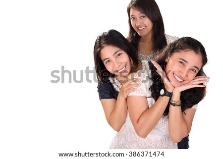 Three playful Asian women making cute pose together, isolated on white background with copy space - stock photo