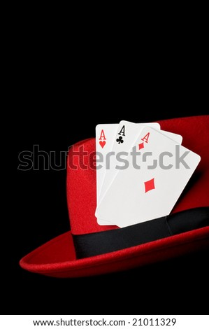 Three playing cards, aces on felt hat, isolated on black background; concept image for gambling - stock photo