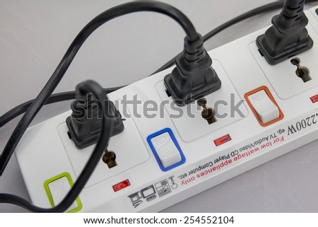 Three plugs plugged into electric power bar - stock photo