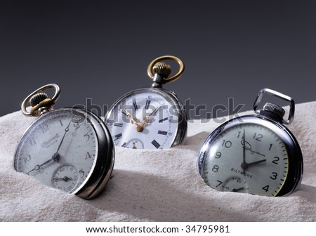 Three pocket watches in sand