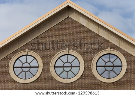 Three portal style windows on brick wall with cloudy blue sky above a copper roof building.