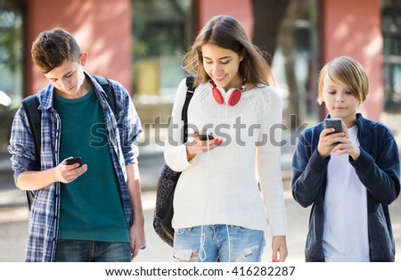 Three positive american teenagers with smartphones in autumn day outdoors