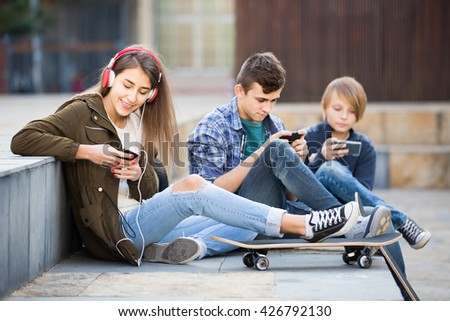 Three positive teenagers with smartphones in autumn day outdoors  - stock photo