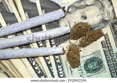 Three pot  joints and three buds of medicinal marijuana on top of a stack of US money, up close. - stock photo