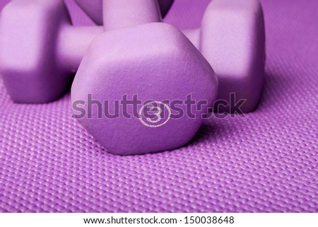 Three pound weight on a purple yoga mat - stock photo