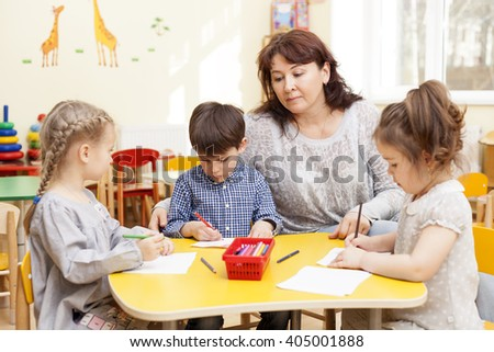 Three preschooler, two girls and a boy, paint pencils at the table. Mature, handsome Caucasian brunette woman, caregiver, watching and smiling. - stock photo