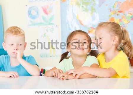 Three preschoolers in the classroom - stock photo