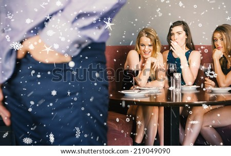 Three pretty friends checking out mans rear against snow falling - stock photo