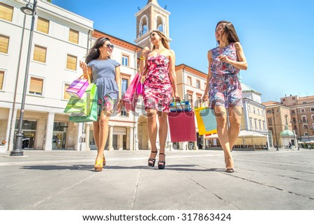 Three pretty girls walking on the streets and holding shopping bags - Best friends shopping on a sale event - Girlfriends talking and smiling - stock photo