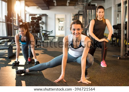 Three pretty girls workout in the gym. - stock photo
