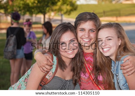 Three pretty teenage girls hugging at student campus - stock photo