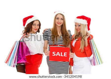 Three pretty young women in Santa's hat with shopping bags stand on a white background. Christmas sale. - stock photo