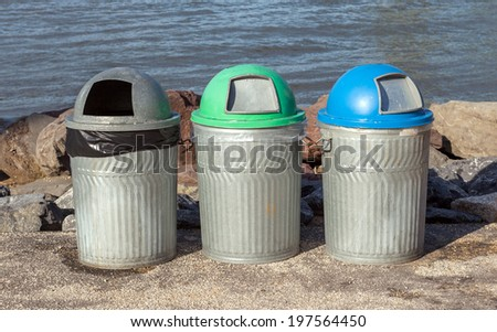 Three public trash cans for different kind of garbage beside riverside, Manhattan Bridge - stock photo