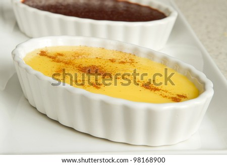 three puddings with chocolate and vanilla in metal tins on a white serving platter - stock photo