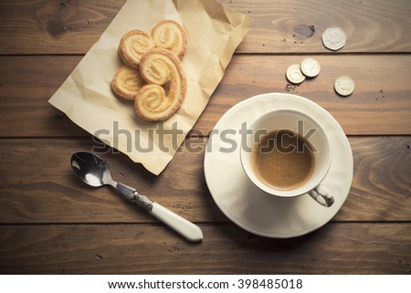Three puff pastry cookies on a kraft paper, a spoon, some coins and a cup of coffee on a wooden table - stock photo
