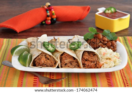 Three pulled pork burritos, carnitas, with a side of slaw and chili beans.  Selective focus on burritos.