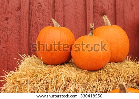 three pumpkins on hay next to red barn - stock photo
