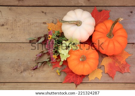 Three pumpkins on wood background with autumn leaves and flowers. Halloween or Thanksgiving decor.