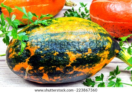 Three pumpkins with green parsley on wooden table - stock photo