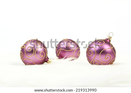 Three purple christmas balls with gold lines on white background - stock photo