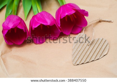 three purple tulip and paper heart with place for text - stock photo
