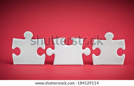 three puzzle pieces on red background - stock photo
