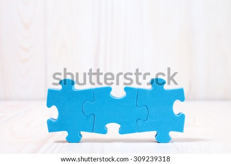 Three puzzle pieces on white wooden background. With copy-space for text - stock photo