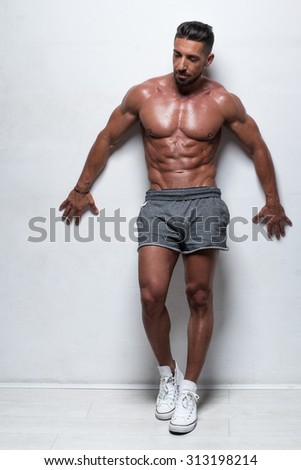 Three Quarter Length Portrait of Muscular Man Standing Shirtless with Hand on Hip Wearing Gray Athletic Shorts in Studio with White Background and Looking to the Side - stock photo