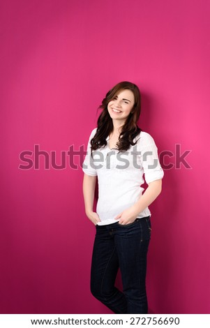 Three Quarter Length Portrait of Smiling Young Brunette Woman Wearing Jeans and White Top Leaning Against Bright Pink Wall - stock photo