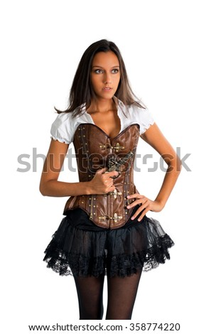 Three Quarter Length Portrait of Young Brunette Woman Wearing Old Fashioned Western Costume with Corset and Tutu Holding Antique Pistol and Standing in Studio with Hand on Hip in White Studio - stock photo