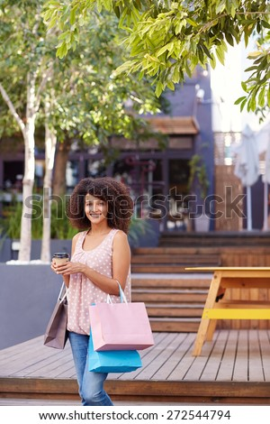 Three quarter length shot of a pretty mixed race woman standing outdoors holding a takeaway coffee and bags of shopping - stock photo