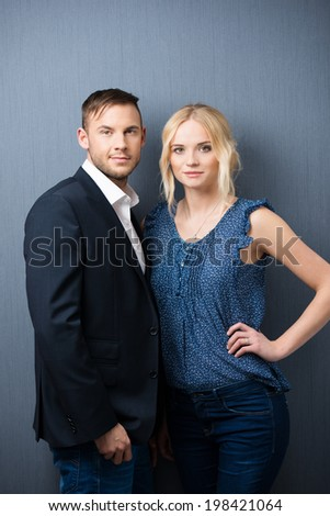 Three quarter portrait of an attractive stylish confident young couple standing close together looking at the camera against a grey background - stock photo
