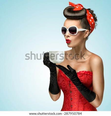 Three-quarter portrait of glamourous pinup girl wearing vintage gloves and red ribbon in her hair, holding a cup of hot coffee or tea and cooling it. - stock photo
