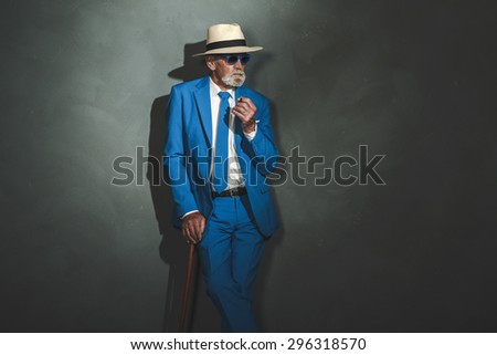 Three-Quarter Shot of a Middle Aged Businessman with Cane Leaning Against Gray Wall and Looking Into the Distance. - stock photo