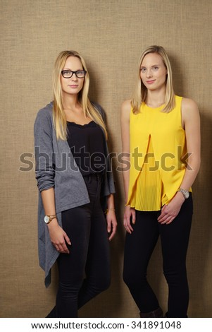 Three Quarter Shot of Two Young Fashionable Women Leaning Against Brown Wall and Looking at the Camera. - stock photo