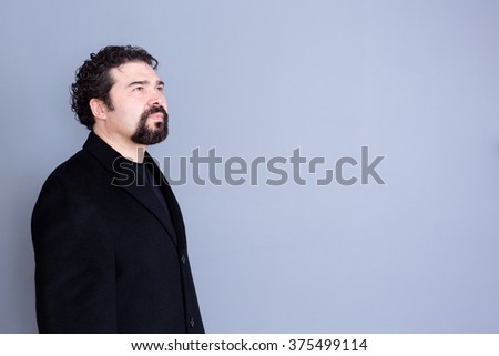 Three quarter view of hopeful attractive dark haired and bearded middle aged male in black shirt and blazer looking away over gray background with copy space