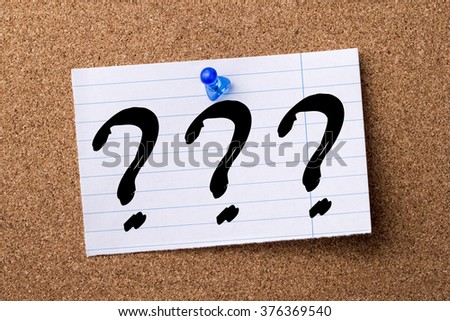 Three question marks - teared note paper  pinned on bulletin board - horizontal image - stock photo