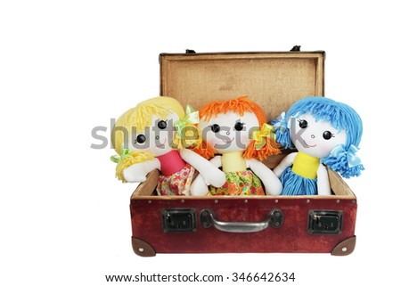 Three rag dolls in a vintage suitcase isolated on white