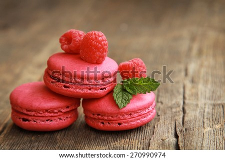 Three raspberry macaroons on a wooden table with fresh fruits and mint - stock photo